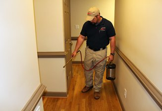 Exterminator Spraying Home for Pest Control